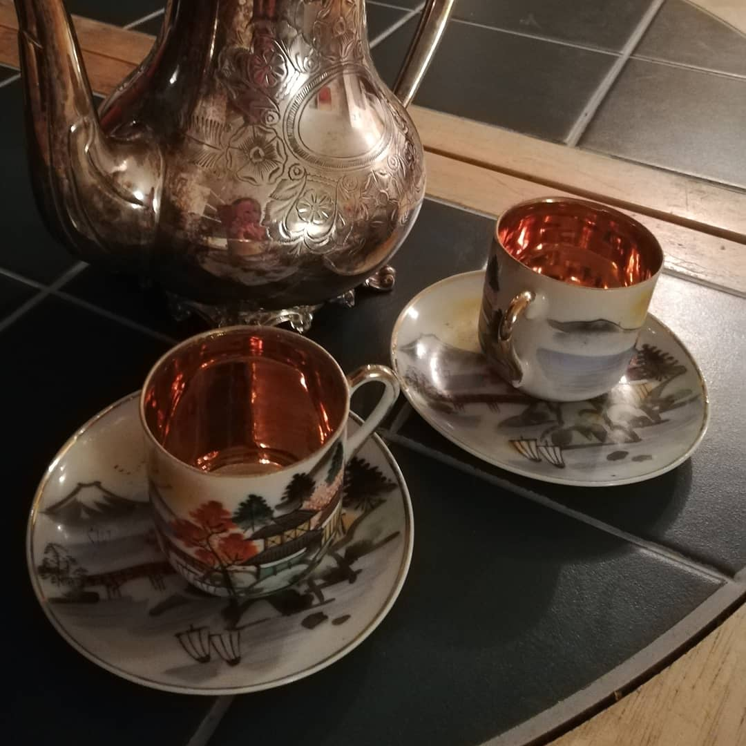 Two colourful coffee cups and a silver coffee pot. These tiny cups are used during the tastings