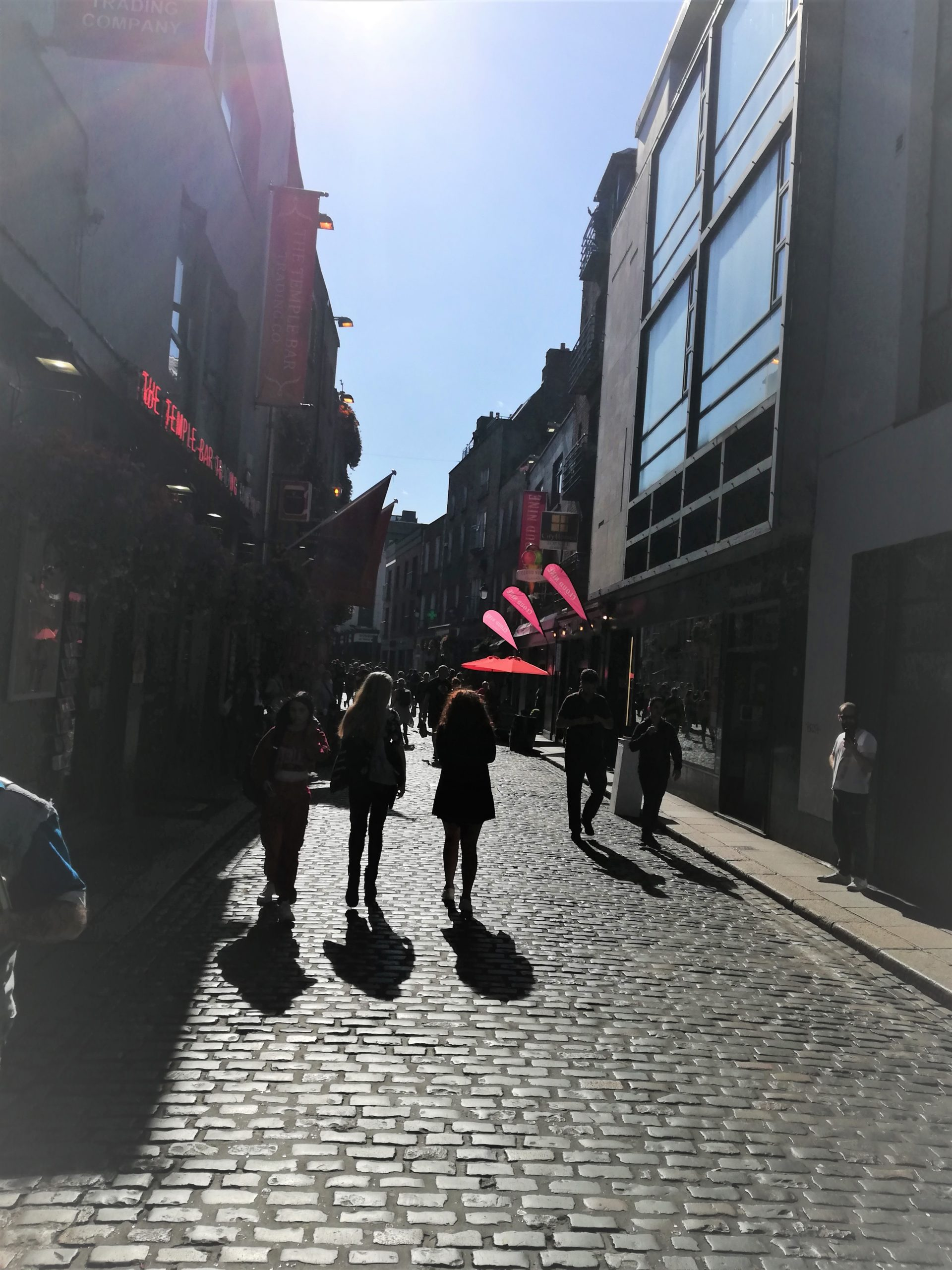 A cobbled street in Temple bar, people walking and blue skys